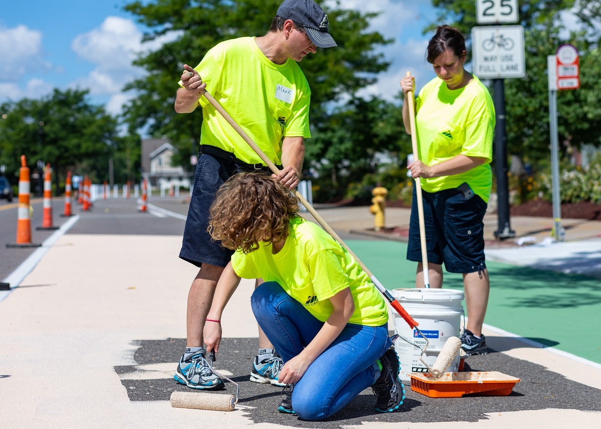 Volunteers paint the bi-directional bikeway buffer at a bus stop in Akron, OH