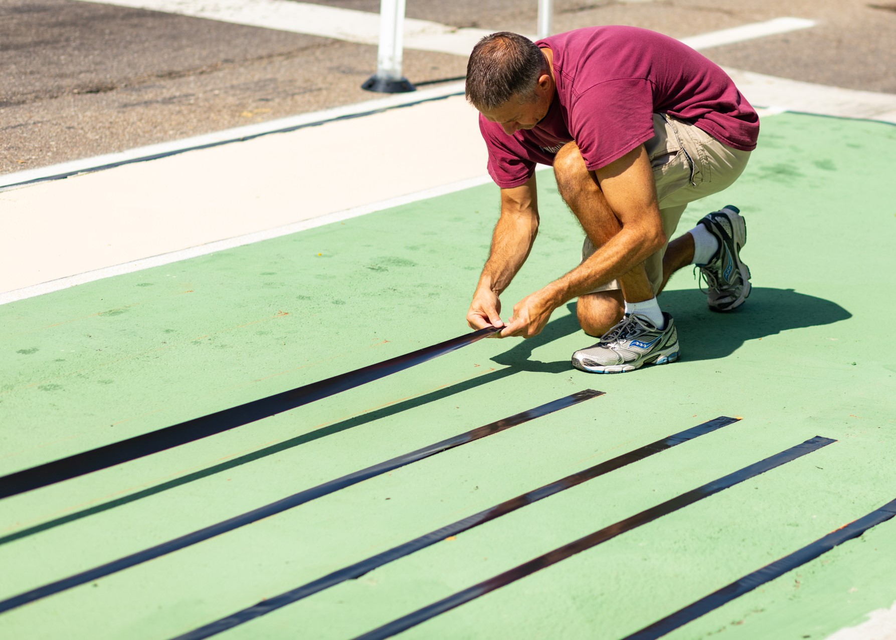 A volunteer outlines new pedestrian crossing markings at a bus stop along the project corridor