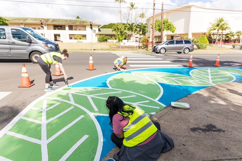 Volunteers help paint one of six curb extensions in Honolulu's Kalihi neighborhood, two of which were at the entrance to Farrington High School (pictured) to slow turning speeds and make accessing the school on foot safer for students
